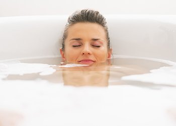For a total immersion bath, fill the tub with warm water and submerge yourself as much as possible for 20-30 minutes